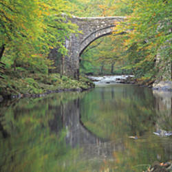 Bridge reflected in the river, Holne Bridge, River Dart, Dartmoor, Devon, England