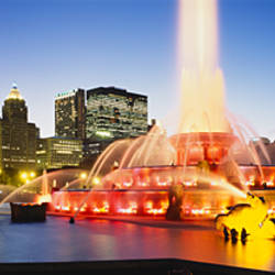 Fountain lit up at dusk with buildings in the background, Buckingham Fountain, Grant Park, Chicago, Illinois, USA