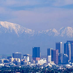 Buildings in a city with snowcapped mountains in the background, San Gabriel Mountains, City of Los Angeles, California, USA